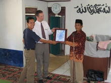 THW Project Leader Martin Abratis (m.) and a UNICEF representative present the official handover certificate to Kahad's head of village (r.) in the village mosque.