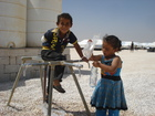 Children at one of the installed water distribution points in the camp.  (show image)