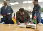 In the presence of THW-President, Mr Albrecht Broemme (left), the Deputy Azerbaijanian Minister for Disaster Prevention, Mr Faig Taghizada, signs the visitor's book of the regional office of Berlin, Brandenburg, Saxony-Anhalt.